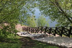Sunny stairs leading down to a blue pond among green trees