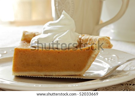 Sunny still life of pumpkin pie with whipped cream and pie server on plate.  Coffee mug and window in background.  Macro with shallow dof.