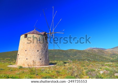 Sunny stone building of a wind mill located on green hills of Greece  #249735553