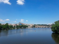 Sunny summer day on Vltava river in Prague with a view on Charles bridge, with castle on the background and small boats in the river