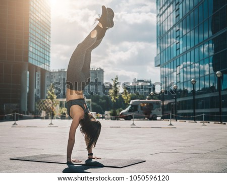 Sunny summer day. Young athletic woman doing handstand on city street among modern skyscrapers. Exercise outdoors, workout. Exercise for balance, yoga, training. Healthy lifestyle.