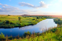 Sunny summer landscape.Green hills,fields and meadows.River Upa in Tula region,Russia.Sunset.Quiet stream.Calm.Warm sunlight.Beautiful clouds in bright  blue sky.