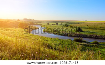 Sunny summer landscape with river.Green hills,fields and meadows.River Upa in Tula region,Russia.Sunrise.Quiet morning.Calm.Warm sunlight.Cloudless clear blue sky.