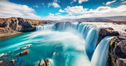 Sunny summer scene of Skjalfandafljot river, Iceland, Europe. Panoramic morning view of Godafoss, spectacular waterfall plunging over a curved, 12m-high precipice, with paths to various viewpoints.