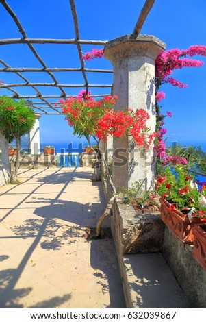 Sunny terrace decorated with red flowers near the sea in Ravello, Amalfi coast, Italy #632039867