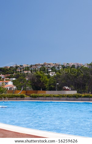 Sunny village of white houses with red roofs pool on foreground