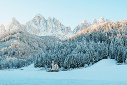 Sunny winter landscape in the morning of Dolomite Alps. St Johann Church with beautiful Dolomiti mountains, Santa Maddalena, Val Di Funes, Dolomites, Italy.