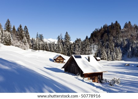 sunny winter landscape with occupied and heated log cabins in the mountains.