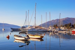 Sunny winter Mediterranean landscape. Yachts and fishing boats on the water. Bay of Kotor (Adriatic Sea), Tivat, Montenegro