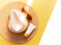 Sunprotection objects. Straw woman's hat with sun glasses and protection cream spf 30 top view on bright yellow background. Beach accessories. Summer Travel Vacation Concept. Sale kit. Copy space.