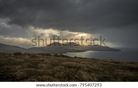 Sunrays illuminate the Dingle Peninsula as clouds bringing rain and sleet start blanketing the skies on Ireland's South West Coast as part of the Wild Atlantic Way