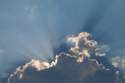 Sunrays reflecting through white clouds in a blue sky