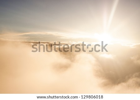 Sunrise above clouds during a flight bright light and colors