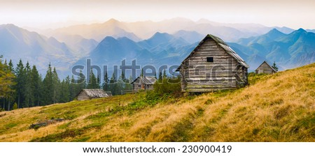 Sunrise above the high mountain foggy valley with old wooden houses on a hill in a mountain forest.