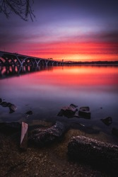 Sunrise along the shores of the Potomac River in Alexandria with the Woodrow Wilson Bridge spanning the river into Maryland.