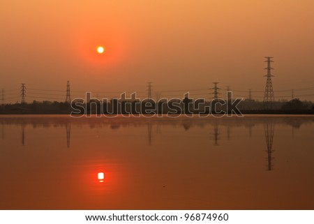 Sunrise and electric pillar with reflection in lake