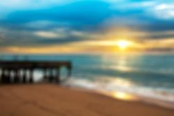 Sunrise and sea beach over the bridge in blurred backgroud