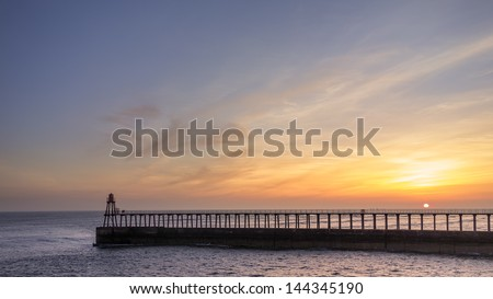 Sunrise and Whitby's pier.