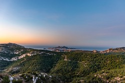 Sunrise at Calanque de Morgiou (Marseille, France): the breathtaking view of the cliff mountain landscape and the island Riou in the distance under the warm soft sunlight