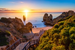 Sunrise at Camilo beach in Lagos, Algarve, Portugal. Wooden footbridge to the beach Praia do Camilo, Portugal. Picturesque view of Praia do Camilo beach in Lagos, Algarve region, Portugal.