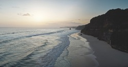 Sunrise at cliff silhouette of ocean bay coast aerial view. Summer nature scenery at sand beach with sun rise up. Nobody seascape at sunlight at sandy shore of Sumba island, Indonesia rocky shoreline