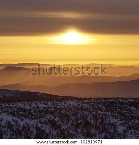Sunrise at czech giant mountains with morning fog on horizon