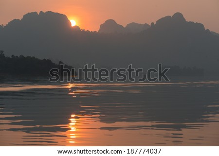 Sunrise at kayak on Rachapapha dam. Khao Sok National Park. Thailand.