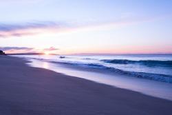 Sunrise at Praia (English beach) de Armacao de Pera in the Algarve in Portugal. Scenic pink sky. Morning ocean view at tourism destination in Portugal.