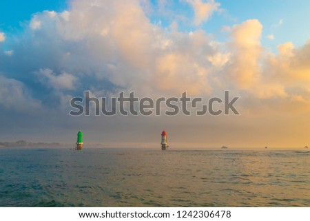 Sunrise at Sanur Beach, Two beacons green and red. Bali, Indonesia.