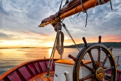 Sunrise at sea on a tall ship classic sailboat.  Close up of the wheel, boom and stern against a dramatic sky and gold sunlight reflections. Concepts: Serenity, prosperity, optimism, positive, future