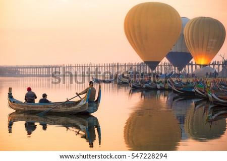 Sunrise at U Bein Bridge with boat and hot air balloon, Mandalay, Myanmar. #547228294
