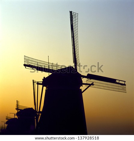 Sunrise behind a group of traditional Dutch windmills on a cold winter morning; Leidschendam, Netherlands