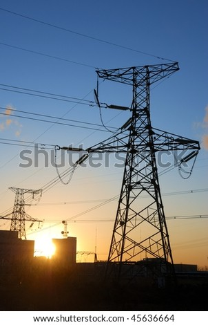 Sunrise behind electricity pylons