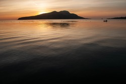 Sunrise behind Holy Island from Lamlash on the Isle of Arran in Scotland.