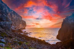sunrise captured at the bluff in Cayman Brac in the Cayman Islands. The light from the sun has lit the rocky cliff face as well as the clouds above