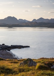 Sunrise casts a glow over the Torridon Hills mountainscape in Wester Ross in the Northwest Highlands of Scotland, as viewed from Gairloch.