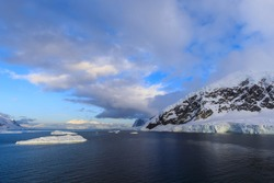 Sunrise cloudscape over the dark sea of Neko Harbour off the Antarctic Continent of Antarctica with a distant view and interesting clouds in the blue sky over snow covered coastal mountains