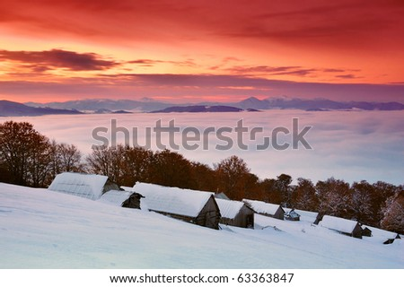 Sunrise in a mountain valley with huts and the first snow in October