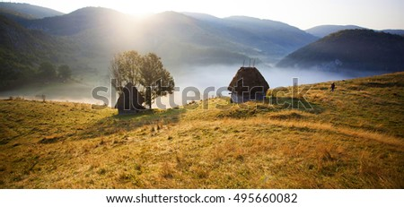Sunrise in autumn mountains - rural landscape with small cottage