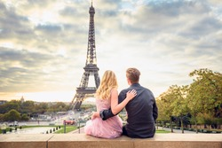 Sunrise in front of the Eiffel tower in Paris. Couple hugging each other and looking at the city from the top of the Trocadero place