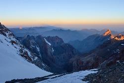 Sunrise in mountains. Reflection of red sun on mountain snow peaks, Fann, Pamir Alay, Tajikistan