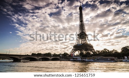 Sunrise in Paris along Seine River, with the Eiffel Tower