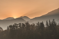 Sunrise in Squamish. Sun poking out behind the mountain in a very smoky foggy day, creating sun beans through the smoke. Pine tress in the foreground
