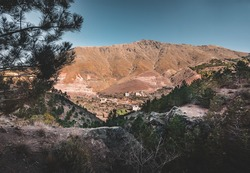 Sunrise in the high Atlas mountains in Morocco near small village of imlil. Blue sky and hiking path. Houses in the background. Travel conept during summer.