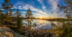 Sunrise in the wild. Dawn. Nature of Karelia. Pine on the shore of Lake Ladoga. Travel to Russia. Republic of Karelia. Islands. Northern nature. The sun above the water.