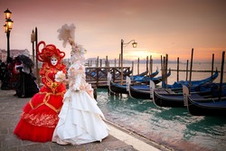 Sunrise in Venice Italy in front of Gondolas on the Grand Canal Beautiful costumed women