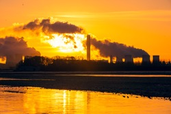 Sunrise in winter over Drax in North Yorkshire with the sun rising behind a water vapour trail from the cooling towers of a Power Plant.  Golden reflections in standing water.  Space for copy.