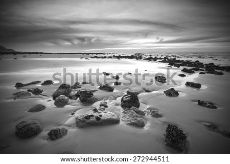 Sunrise landscape on rocky sandy beach with vibrant sky and clouds in black and white