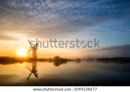 Sunrise landscape over foggy River Thurne looking towards Thurne Mill Windmill