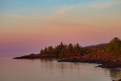 Sunrise landscape with a colorful sky. Lake Superior peninsula with trees and rocks.